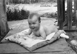 Infant posed on cushion outdoors, n.d.