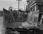 Construction truck lined with shovels, rakes, and pick axes, September 25, 1955