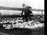 King County Sheriff Matt Starwich destroying bottles of confiscated alcohol, ca. 1925
