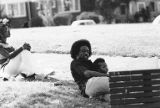 Afro-Americans seated on the grass at the  United Construction Workers Association (UCWA) picnic,...