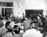 Man speaking to standing-room-only audience at mass meeting at the Seafood Workers Union office in...