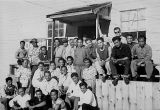 Large group of men, mostly Filipino, outside white building, unidentified cannery, Alaska, ca....