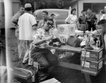 Elmer Ogawa repairing an article of clothing during the American Legion Cathay Post 186 picnic,...