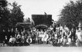 "Group photo of men and women outside a sign that says, ""Fredensborg"", n.d."