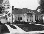 One-story Craftsman style house with hipped roof, symmetrical facade and center entrance, probably...