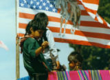Native American children in traditional dress  with an American flag at the Toppenish parade,...