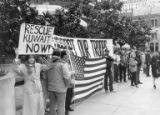 Counter-protesters with signs and an American flag at an anti-Gulf War protest in Seattle,...