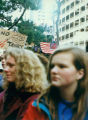 Two women in foreground, with protesters behind them holding signs and flags, at a Gulf War...