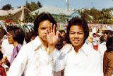 Two young Filipino men, one waving his arm, at unknown outdoor celebration, ca. 1980