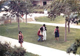 Young people walking on lawn, ca. 1980