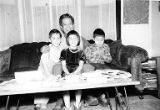 Chris Mensalvas sitting with son Topper Mensalvas, daughter Patsy Mensalvas and Michael, ca. 1956