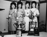Asian American Princess standing with community trophies at the Bush Garden Restaurant, 409...