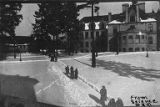 Denny Hall and people walking down snow-covered pathways on the University of Washington campus,...