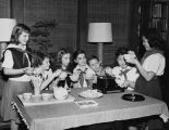 Asian-American girl showing her friends how to use chopsticks at a Campfire Girls farewell dinner,...