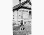 Boy in bathing suit outside of house, probably Seattle, ca. 1905