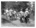 Girls riding on donkeys being led by two boys on foot, probably Seattle, ca. 1905