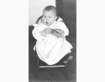 Baby seated in chair and holding stuffed tiger, probably Seattle, ca. 1905