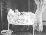 Baby in bassinette with basket of toys on floor below, probably Seattle, ca. 1905