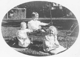 Two children and baby with Iron Clad brand wagon and small wooden wagon, probably Seattle, ca. 1905