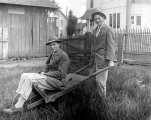 Frank Bonds wheeling himself in wheelbarrow, McMinnville, ca. 1909