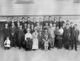 Tatsuya, Kan and Clarence Arai with group in front of building, ca. 1910 to 1912