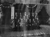 Tatsuya Arai with group of Japanese men, and several children in front of the Japanese Daily News...