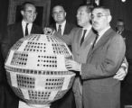 Newton Minow, James Webb, and Senators Warren G. Magnuson and John Pastore looking at model for...