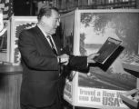 Senator Warren G. Magnuson looking at a brochure for Washington state at the U.S. Trade Center,...