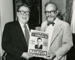 Magnuson and unidentified man posing with campaign poster from his first Congressional campaign,...