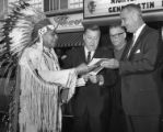 Man in Native American dress making presentation to President Lyndon B. Johnson as Senator Warren...