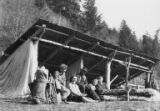 Group sitting under wood structure, Humes Ranch, Olympic Peninsula, 1944