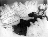 Lucian Phelps (female impersonator) reclining on a bed of feathers, Vancouver B.C., n.d.