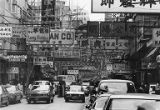 Automobiles, street signs, scaffolding and advertisements along a busy road, Hong Kong, April 1982