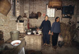 Stanford Chen's relatives in kitchen with cat and pig, Hoi Yin Village, April 1982