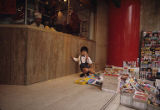 Boy sitting near stack of magazines on sidewalk outside butcher shop, Hong Kong, China, April 1982