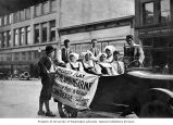 Men and women in traditional costumes seated in open car with banner advertising play by the...
