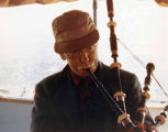 Edward Cox playing the bagpipe aboard his boat Juno off Decatur Island, San Juan Islands, ca. 1958