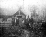 Five men in front of cabin, one holding a sickle, n.d.