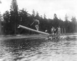 YMCA boy's camp on Orcas island showing young men lining up to dive from log mounted on small...