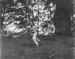 YMCA boy's camp on Orcas island showing boys playing baseball on grassy field, 1910