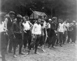 YMCA boy's camp on Orcas island showing young men in knickers lined up at a sporting activity, 1910