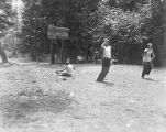 YMCA boy's camp on Orcas island showing three boys in gunny-sack race on grassy field, 1910