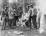 YMCA boy's camp on Orcas island showing young men cooking on small campfire in woods with sleeping...
