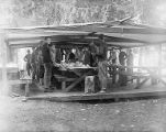 YMCA boy's camp on Orcas island showing boys lined up at tables in canvas dining shelter, 1910