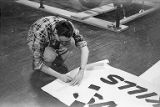 Wess Peterson drawing on banner, Seattle Auto Show, March, 1953