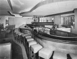 Lounge interior with long curved bar with nailhead trim, circa 1950s