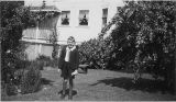 Bobby Sanders standing in yard near trees at 5023 15th Ave NE, Seattle, circa 1940-1941