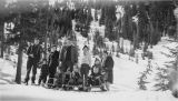 Group of adults and children on snowy hilltop with sleds, Naches Pass, March 1941