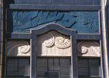 Upper window ornamentation featuring swirl and zig zag patterns and view of parapet with suburst...