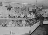Meat cutters and a customer at a meat market in Bremerton, Washington, circa 1950